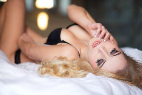 Blonde Frau in schwarzen Dessous liegt mit dem Rücken auf dem Bett