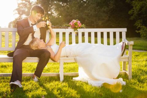 After-Wedding-Shooting bei tiefstehender Abendsonne im Schwetzinger Schlossgarten auf einer Parkbank mit coolem Paar und Bierflaschen